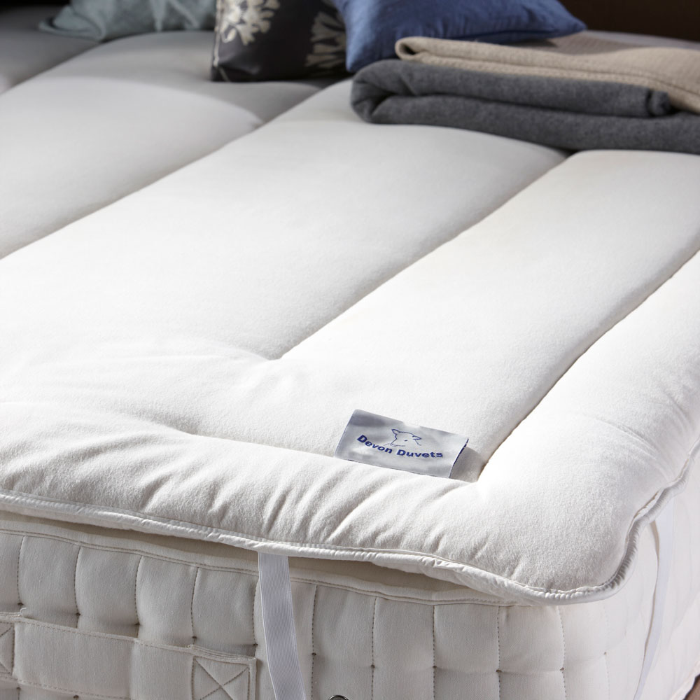 How can a wool mattress topper help keep you cool in the warmer months?